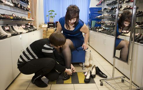 раб меряет обувь госпожи в обувном супермаркете она его
